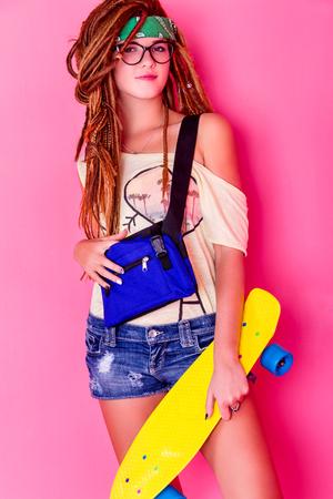 rastas: Pretty young girl with dreadlocks holding yellow skateboard