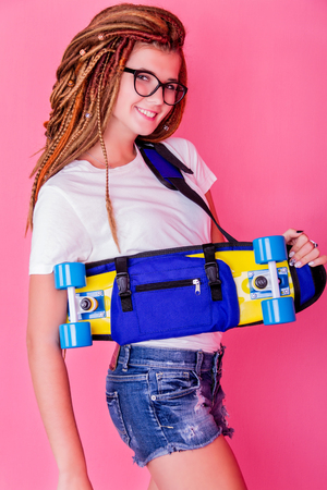 Pretty young girl with dreadlocks holding the skateboard and smiling