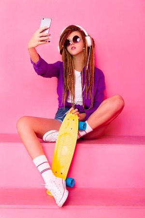 Pretty girl sitting with the yellow skateboard listening to the music and taking selfie