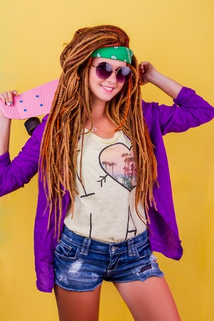 Pretty girl with dreadlocks and green do-rag holding rose skateboard and smiling