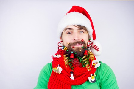strands: Guy dressed as Santa wearing beard decorated with colorful christmas toys, tiny balls and strands Stock Photo