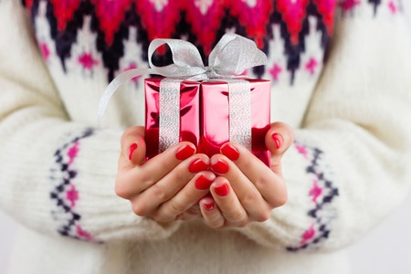 Girl holding decorated gift with red paper and white ribbon Stockfoto