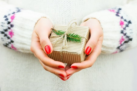 Girl in mittens holding decorated gift with string and branch of christmas tree Stock Photo