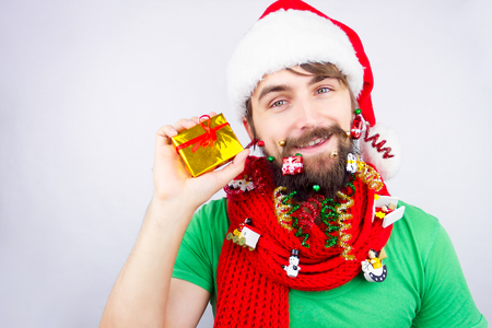 strands: Guy dressed as Santa wearing beard decorated with colorful christmas toys, tiny balls and strands, delighted with the present