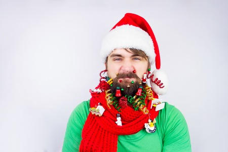 strands: Guy dressed as Santa wearing beard decorated with colorful christmas toys, tiny balls and strands and frowning