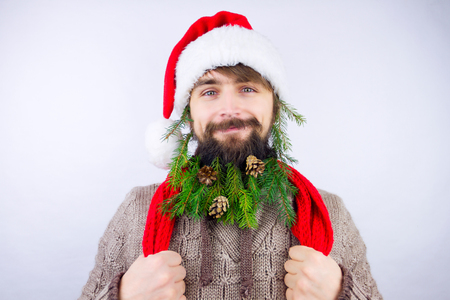 Guy dressed as Santa wearing beard decorated with green branches from christmas tree and several cones Stock Photo