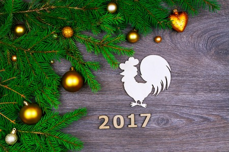 next year: Green branches from christmas tree decorated with colorful balls,  wooden number of the next year and figure of rooster isolated on wooden background