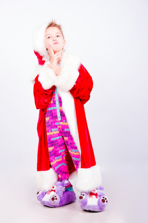 wearing slippers: Boy dressed as Santa Claus wearing pyjamas, soft slippers, santas hat and coat being thoughtful