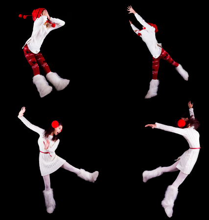Young woman gymnast dressed as santas elf jumping in the air without visible ropes isolated on black background Stock Photo