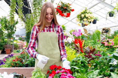 airbrush: Girl standing in the greenhouse surrounded by colorful plants and sprinkling flowers with airbrush