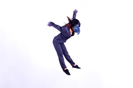 Young woman wearing mask of parrot jumping in the air