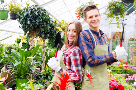 Florists at work. Girl and guy standing back to back holding gardening tools Stock Photo