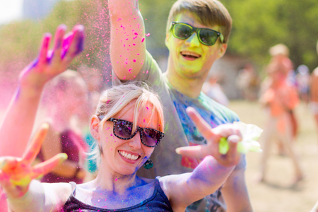 Girl and guy wearing sunglasses having fun during Holifest throwing colorful powder in the air