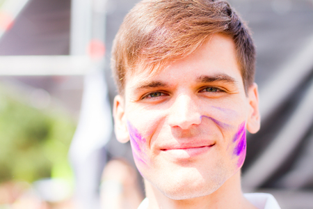 pink powder: Portait of guy stained with pink powder smiling during Holifest Stock Photo