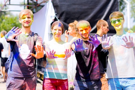 Young people stained with colorful powder showing their hands having fun during Holifest