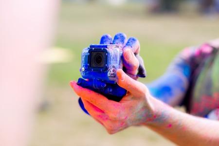 Guy holding camera shooting Holi Fest celebration