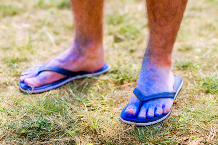 Body parts.Close-up shooting of guys feet wearing blue flip-flops stained with colorful powder