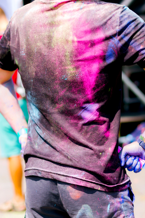 Conceptual shooting of guys back stained with colorful powder  during Holifest