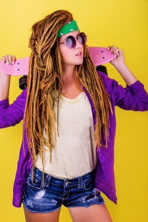 Pretty girl with dreadlocks and green do-rag holding pink skateboard and smiling Stock Photo
