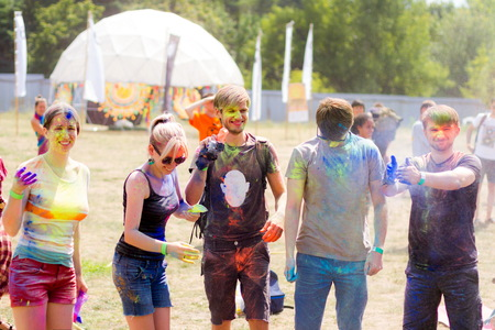 Young people stained with colorful powder having fun during Holifest