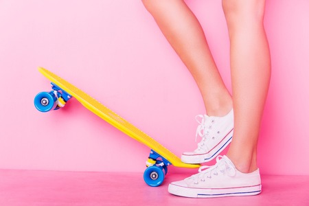 Conceptual shooting of girl's feet standing on the skateboard Stock Photo