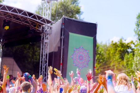 Young people having fun during Holifest throwing colorful powder in the air near the stage Stock Photo