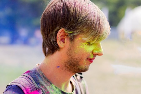 Bright portrait of a guy stained with colorful powder during Holi celebration.