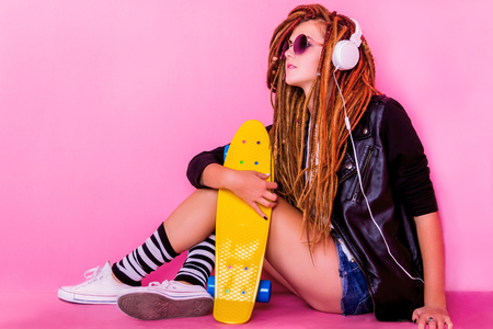 Pretty young girl sitting with the skateboard and listening to the music Stock Photo
