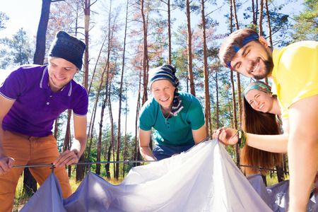 sustainable tourism: Young tourists putting up a tent in the woods Stock Photo