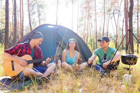 sustainable tourism: Young tourists sitting near the tent playing guitar and making meal