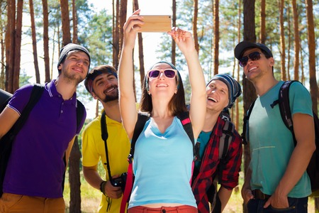 Young tourists taking selfie with the smartphone in the woods Stock Photo