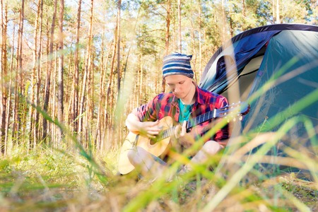 sustainable tourism: Guy sitting near the tent in the forest and playing guitar