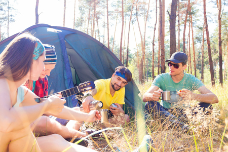 sustainable tourism: Tourists sitting near the tent playing guitar and drinking tea