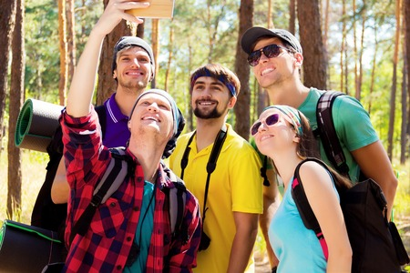 sustainable tourism: Young tourists taking selfie with the smartphone in the woods Stock Photo