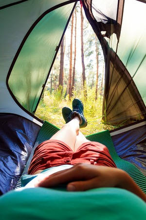 sustainable tourism: View from the tent. Girl lying in the tent on the sleeping mat. Stock Photo