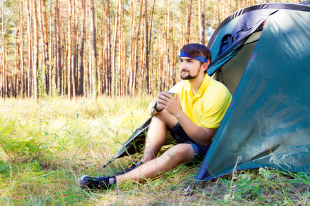 sustainable tourism: Guy sitting near the tent in the forest and drinking tea Stock Photo