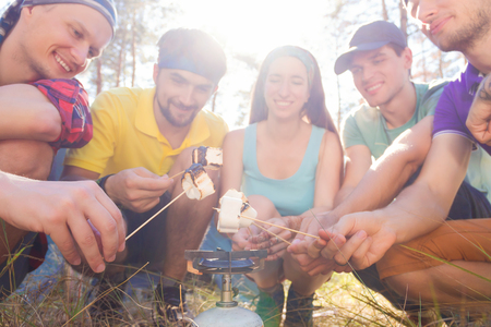 sustainable tourism: Young tourists roasting marshmallow in the forest
