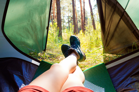 View from the tent. Girl lying in the tent on the sleeping mat. Stock Photo