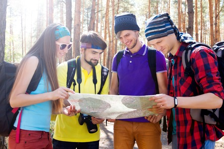 sustainable tourism: Girl and guys trying to find way with the help of map and compass