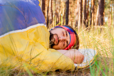 Guy sleeping in the sleeping-bag on the ground in the woods Stock Photo