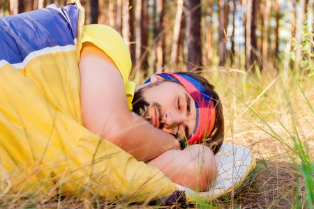 sustainable tourism: Guy sleeping in the sleeping-bag on the ground in the woods Stock Photo