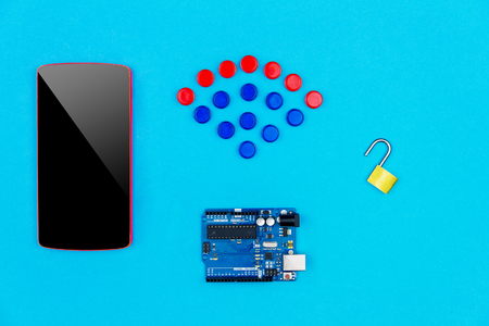 hacked: Concept hacked. Top view of smartphone, microchips, microcontroller and unlock lock on blue background with wifi symbol from colorful hardware buttons