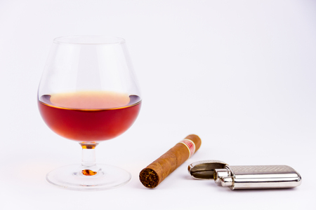 Cognac glass and cigar with lighter isolated on white background