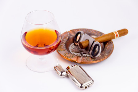 Cognac glass and cigar with ashtray and lighter isolated on white background