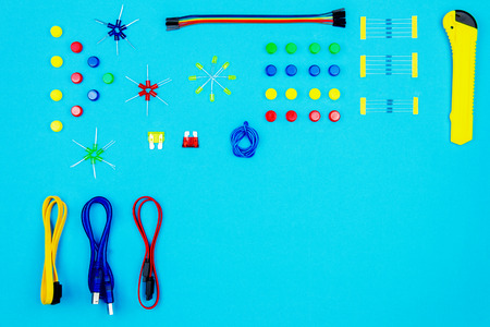 Colorful connectors: usb, sata; resistors, buttons and light-emitting diode on blue background. Minimalism and perfectionism concept