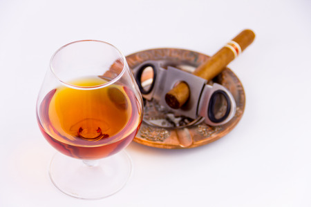 Cognac glass and cigar with ashtray isolated on white background