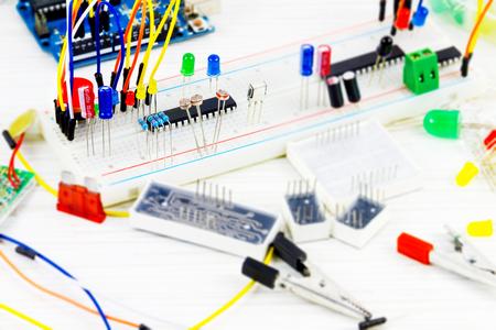 placa de protótipo com microcontroladores, chips, resistores e diodos emissores de luz no desktop branco de engenheiro de hardware
