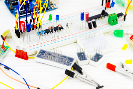 Prototype board with microcontrollers, chips, resistors and light-emitting diodes on white desktop of hardware engineer Stockfoto