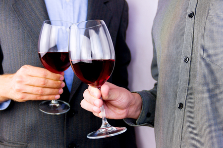 Close-up of mens  hands cheering up with glasses of wine