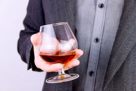 Close-up of mans  hand holding glass of cognac
